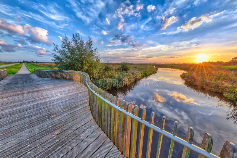 在木楼梯栏杆的生动的日落 免版税库存图片