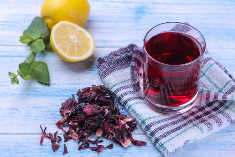 在木槿和柠檬玻璃和叶子的茶karkade在一张蓝色桌上 免版税库存图片