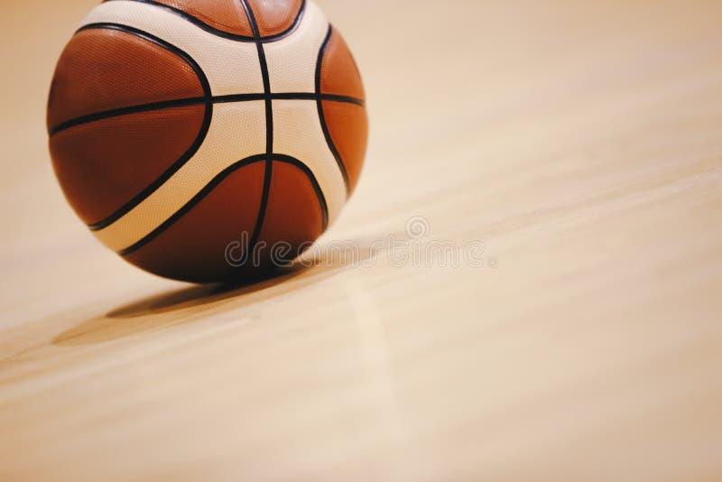 在木法院地板关闭的篮球与被弄脏的竞技场在背景中 免版税库存照片