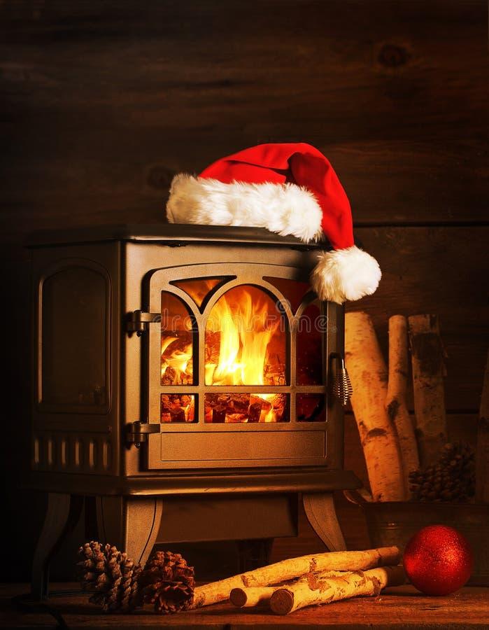 在木火炉的圣诞老人帽子 免版税库存照片
