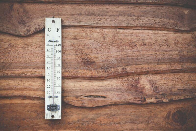 在木热世界的墙壁、的概念和天气上的摄氏度校准的木温度计 库存图片