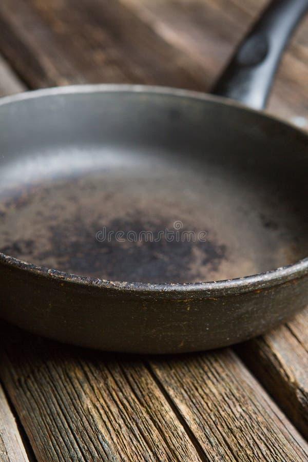在木烹饪背景的空的铁煎锅 库存图片