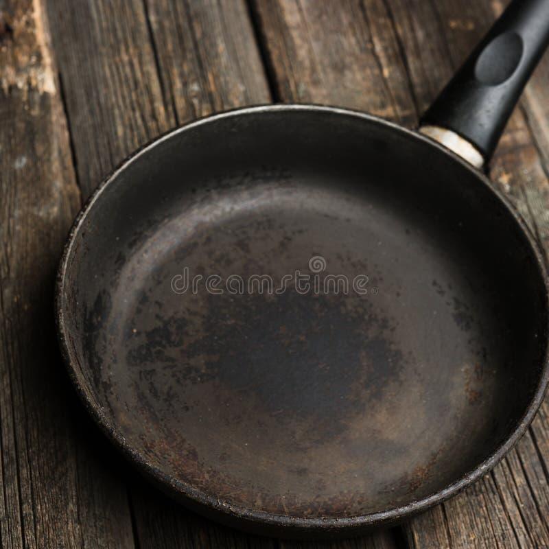 在木烹饪背景的空的铁煎锅 免版税库存图片