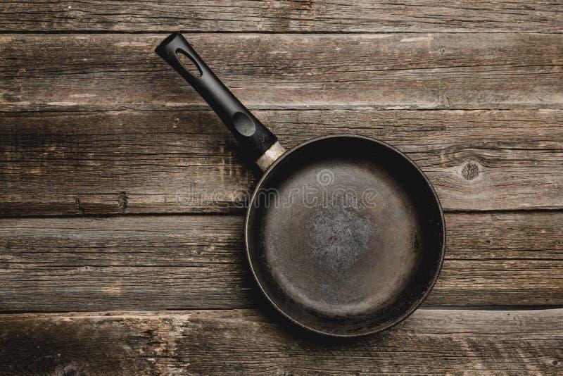 在木烹饪背景的空的铁煎锅 免版税库存照片