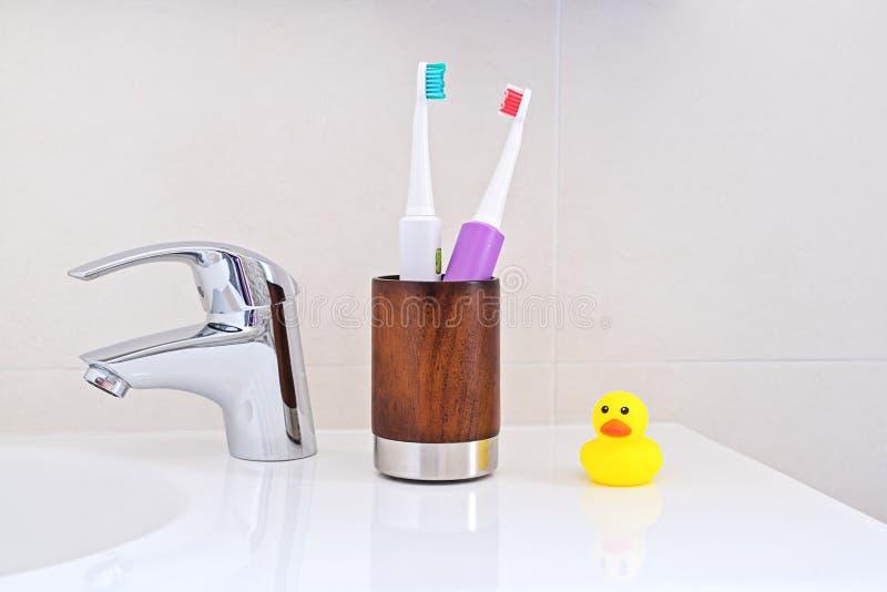 在木玻璃的两把电牙刷在水槽在卫生间里 库存照片