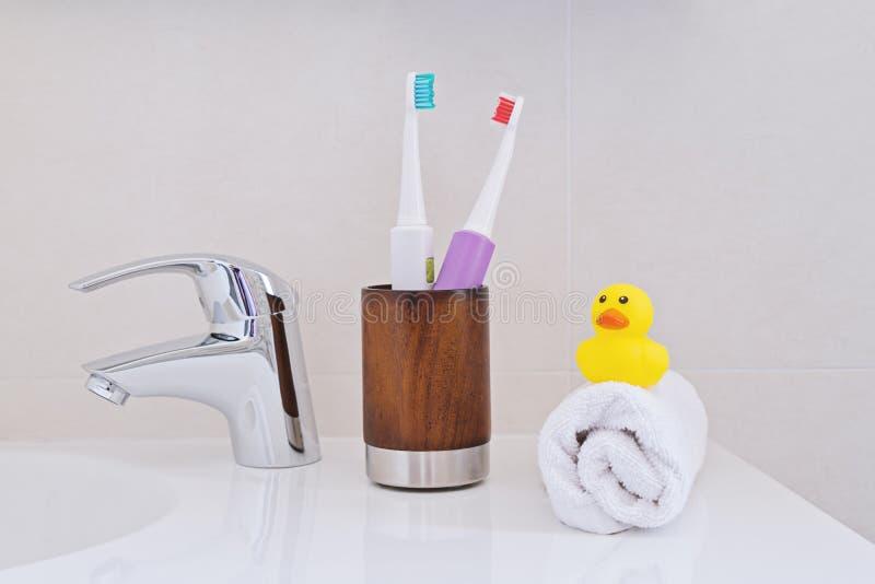 在木玻璃的两把电牙刷在水槽 免版税图库摄影