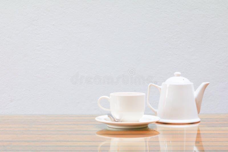 在木玻璃的桌和水泥墙壁背景上的咖啡杯和茶壶白色 免版税库存照片