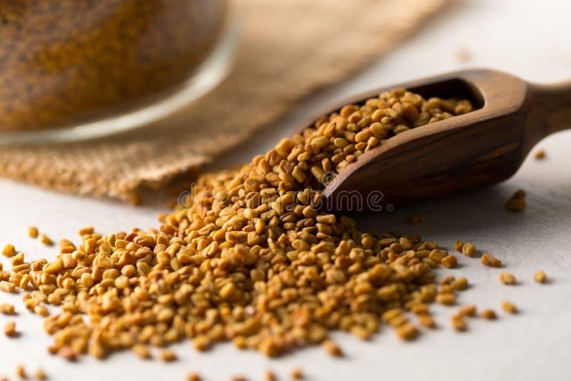 在木瓢的干,未加工的胡芦巴籽有在白色木桌背景的存贮玻璃瓶子的 库存照片