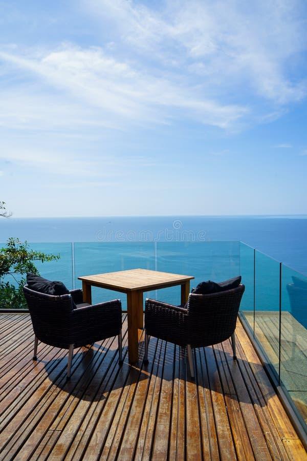 在木甲板和玻璃阳台有全景安达曼海洋海视图,绿色树的表和藤条室外扶手椅子设置 免版税库存照片
