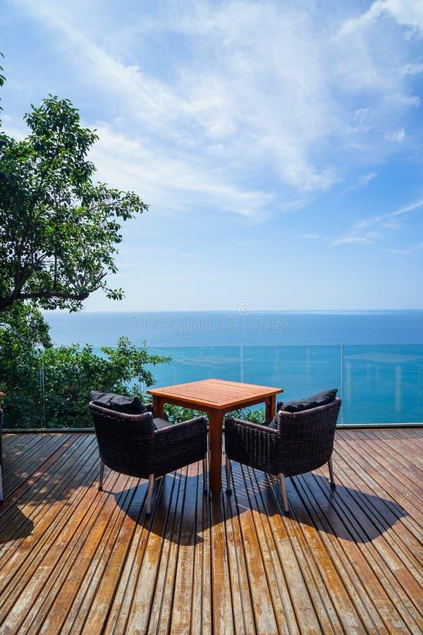 在木甲板和玻璃阳台有全景安达曼海洋海视图,绿色树的表和藤条室外扶手椅子设置 库存照片