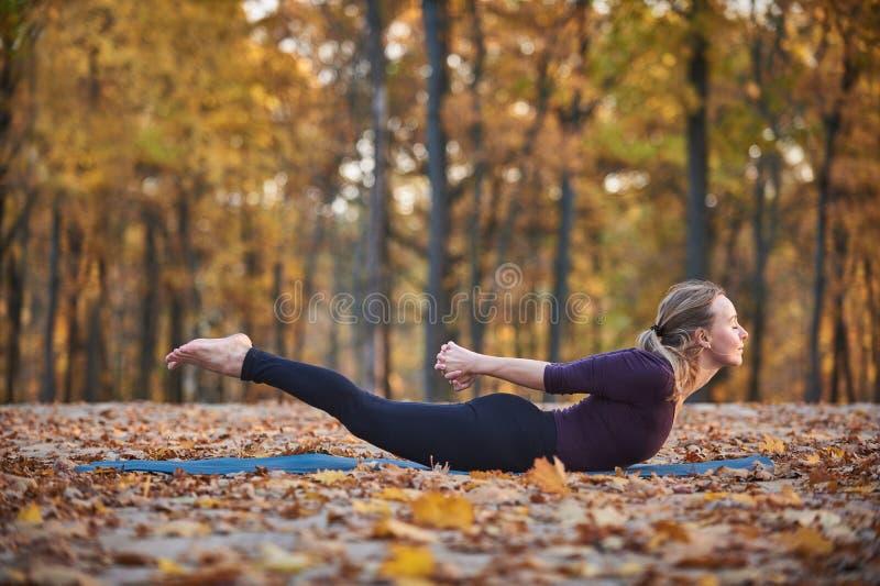 在木甲板的美好的少妇实践瑜伽asana Salabhasana蝗虫姿势在秋天公园 免版税库存图片
