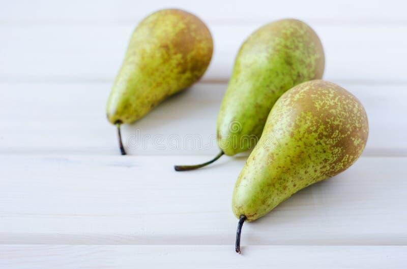 在木白色桌上的三个绿色梨 免版税库存照片