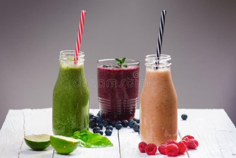 在木白色背景的蓝莓, spinachy和橙色圆滑的人 杯圆滑的人用莓果和薄菏 莓果、叶子和林 库存图片