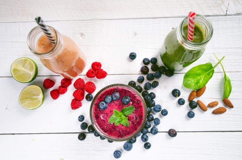 在木白色背景的蓝莓, spinachy和橙色圆滑的人 杯圆滑的人用莓果和薄菏 莓果、叶子和林 免版税图库摄影