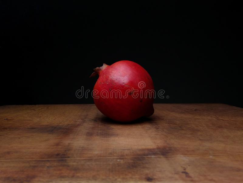 在木的桌上的红色成熟石榴 库存图片