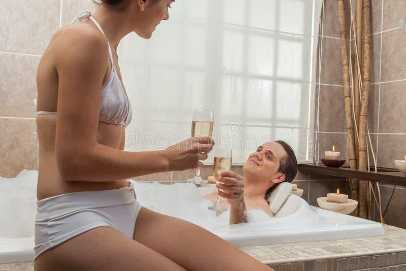 在木盆饮用的香槟的夫妇 免版税库存照片