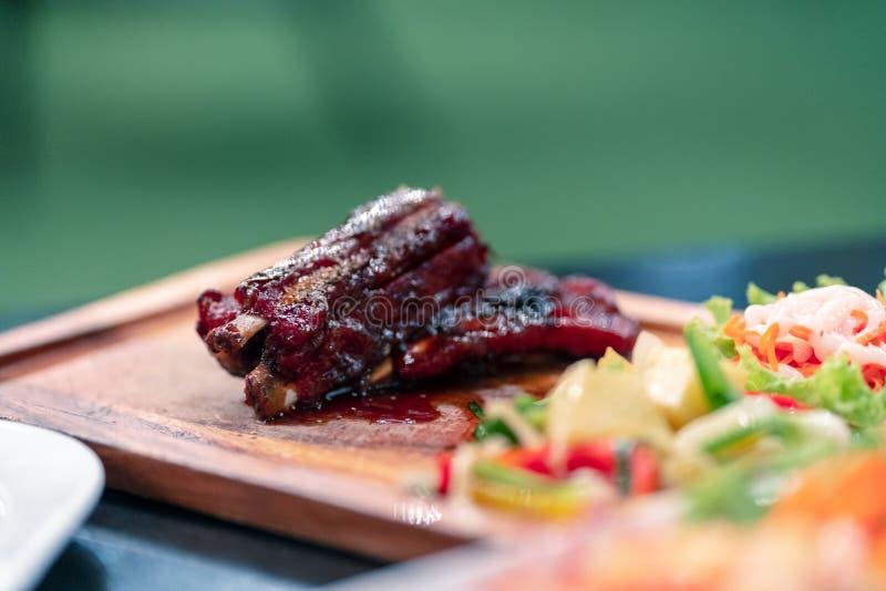 在木盘子的焦点可口猪肉裂口在餐馆在晚上 图库摄影