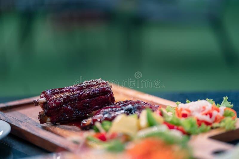 在木盘子的焦点可口猪肉裂口在餐馆在晚上 库存图片