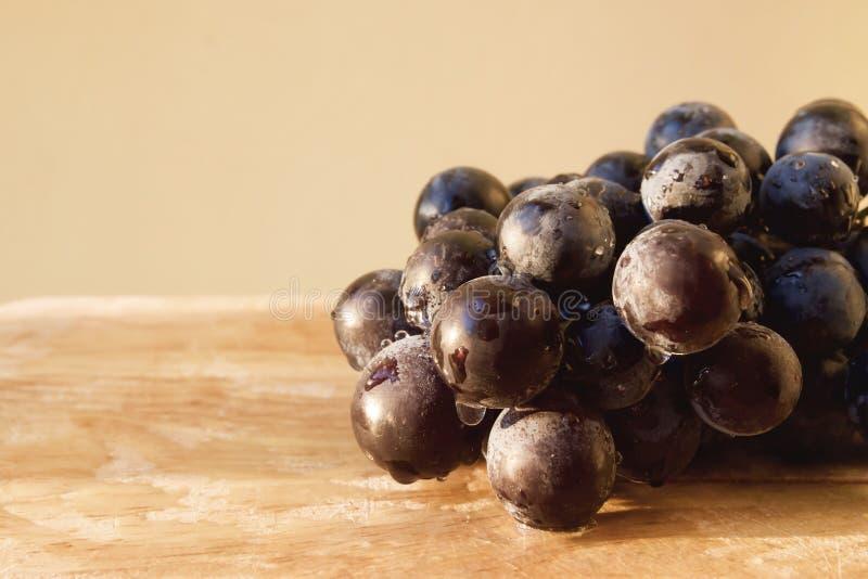 在木盘子的黑葡萄有水下落和阳光的 切的背景剪切果子半菠萝 图库摄影