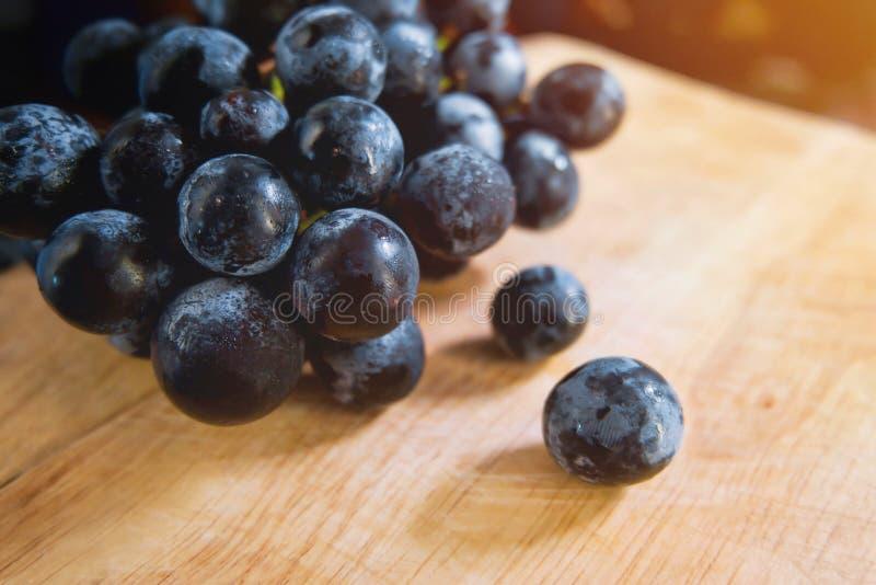 在木盘子的黑葡萄有阳光的 切的背景剪切果子半菠萝 免版税库存图片