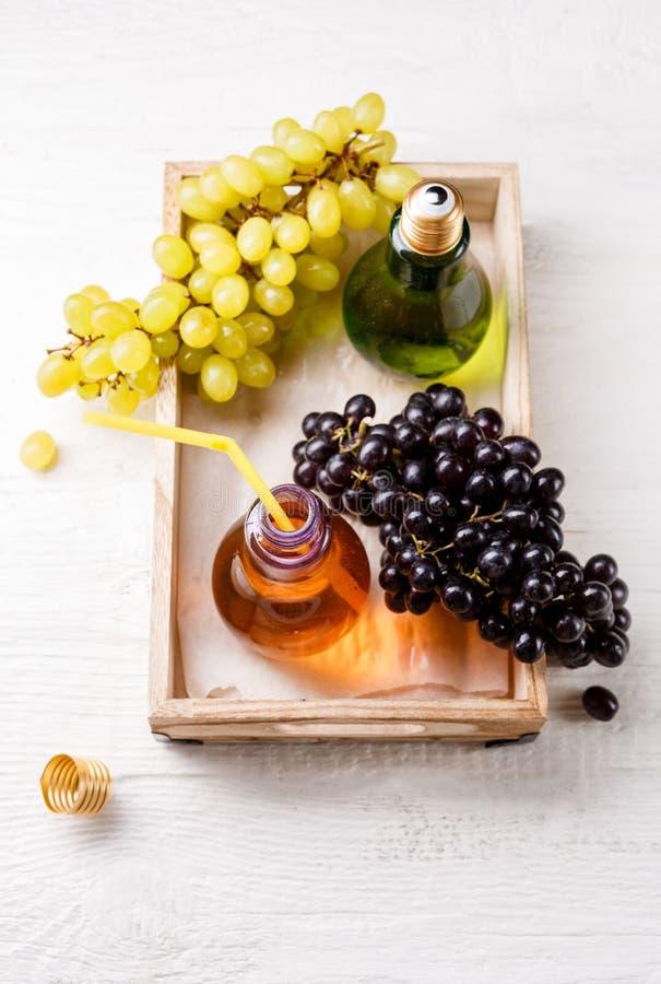 在木盘子顶部的照片用绿色和黑葡萄,两个瓶汁液 免版税库存照片