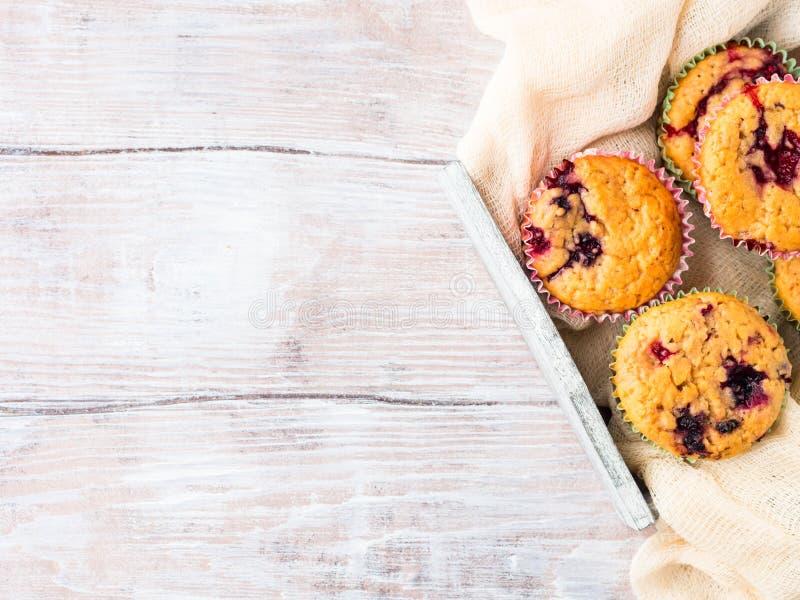 在木盘子餐巾早餐的莓果松饼 图库摄影