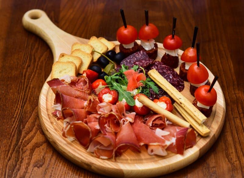 在木盛肉盘的午餐肉 食物盘子用可口切的火腿和点心用蕃茄,午餐肉概念 吃和 图库摄影