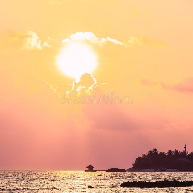在木码头、海岛和太平洋的日落在马尔代夫 免版税库存照片