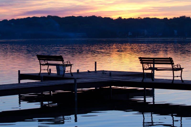 在木码头的现出轮廓的长凳在日落 免版税库存图片