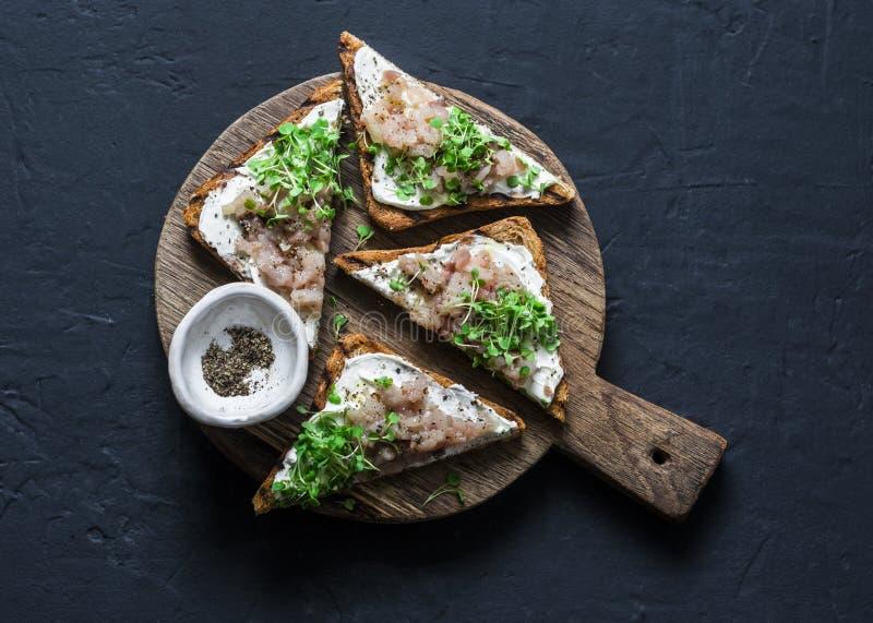 在木砧板的抽烟的鲭鱼和奶油奶酪bruschetta在黑暗的背景,顶视图 可口的开胃菜 库存照片