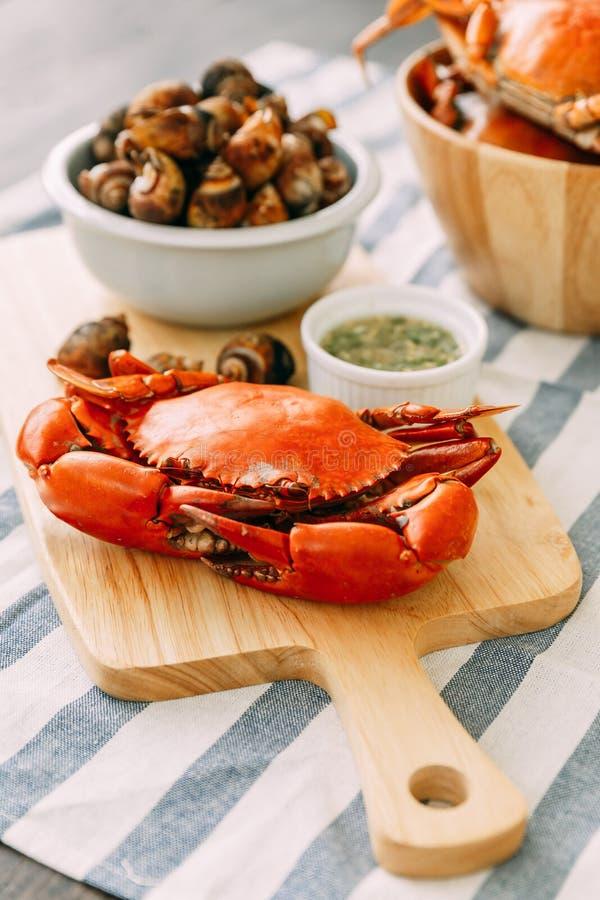 在木砧板的被蒸的巨型泥螃蟹服务用泰国辣海鲜调味料和烤Laevistrombus在壳的Canarium 库存照片
