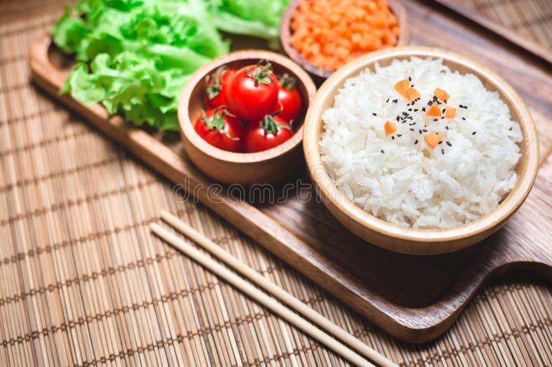 在木碗和筷子的白米用红萝卜、黑芝麻和蕃茄菜在木板 健康食物和 免版税图库摄影