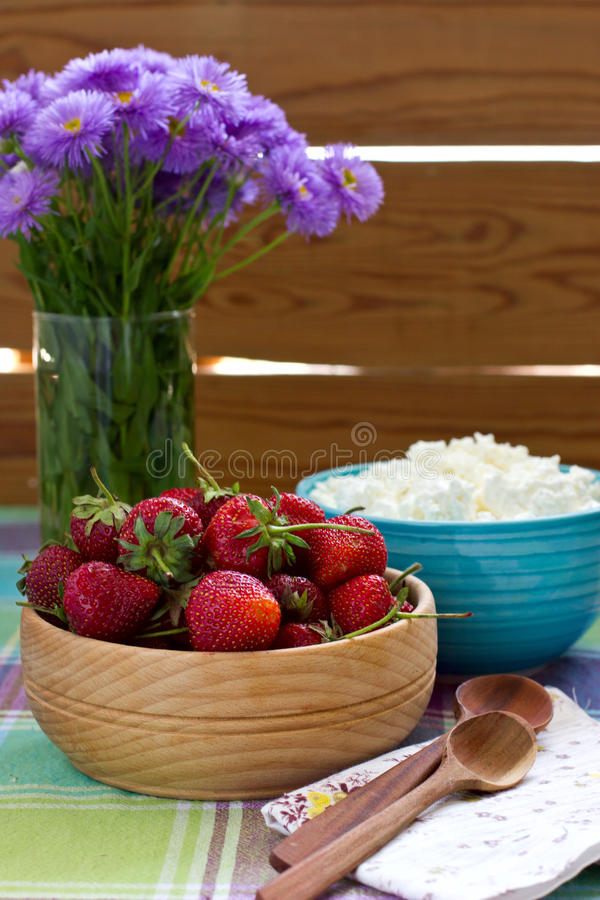 在木碗和酸奶干酪的草莓 库存照片