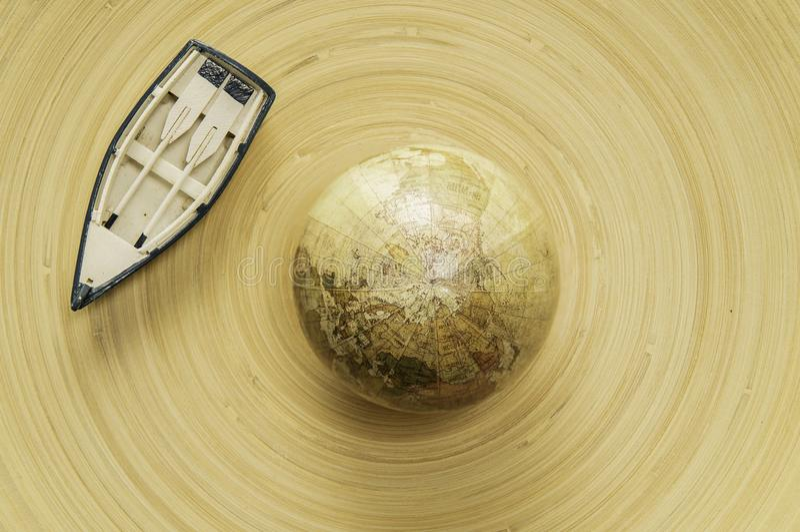 在木碗圈子的小船有地理地球世界地图的 库存照片