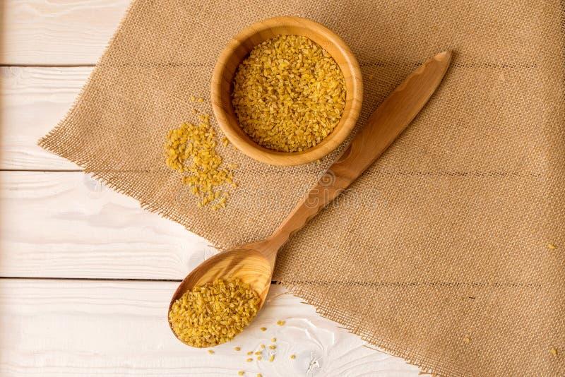在木碗的干碎小麦有在桌上的匙子的 库存照片