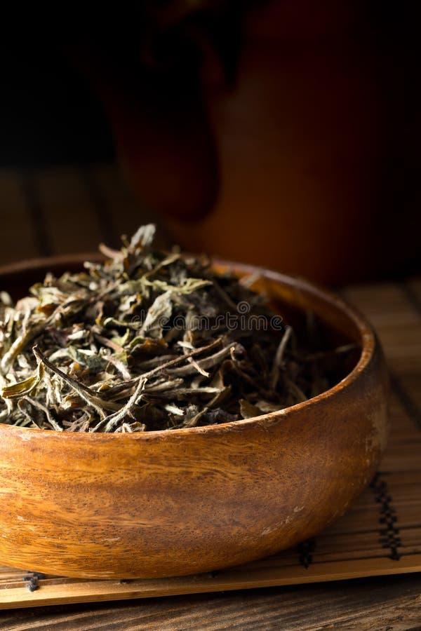 在木碗的干,未加工的白色茶叶在竹席子背景 免版税库存照片