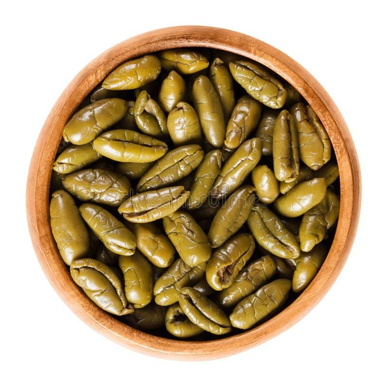 在木碗的干绿橄榄一半在白色 免版税库存照片