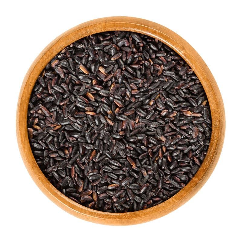 在木碗的有机黑米在白色 图库摄影