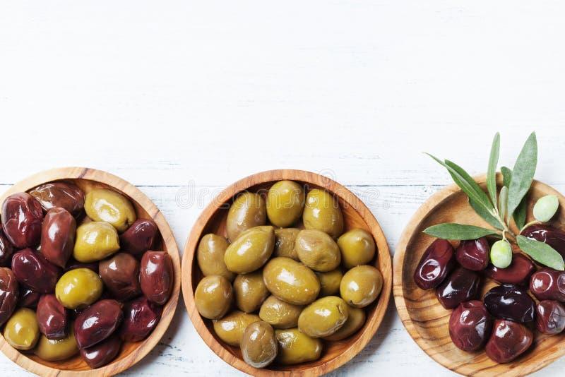 在木碗的橄榄在白色木台式视图 库存照片
