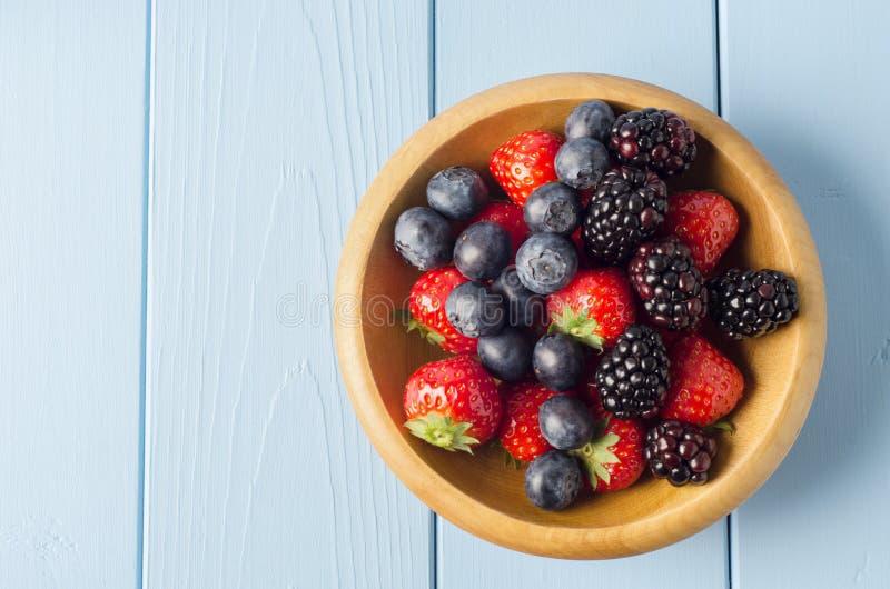 在木碗的混杂的莓果在浅兰的木Planked选项 库存图片