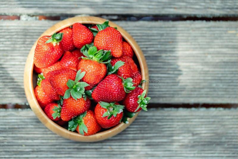 在木碗的甜新鲜的水多的有机成熟草莓木表面上在户外明亮的好日子 免版税库存图片