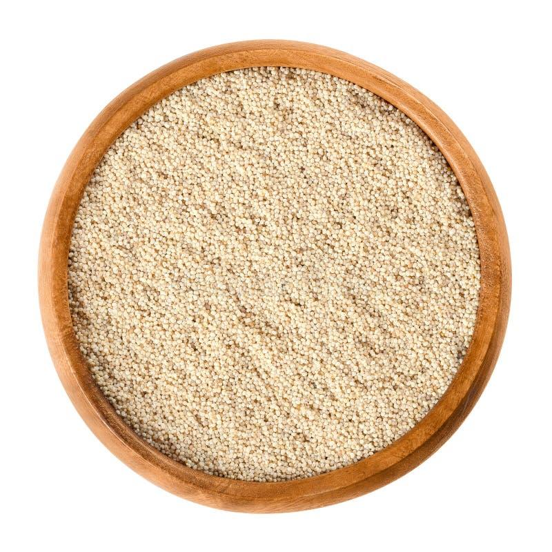 在木碗的白罂粟种子在白色 库存图片