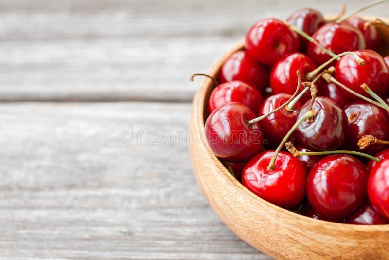 在木碗的红色成熟樱桃莓果 r 图库摄影