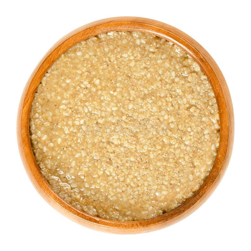 在木碗的自创tahini芝麻酱在白色 库存照片