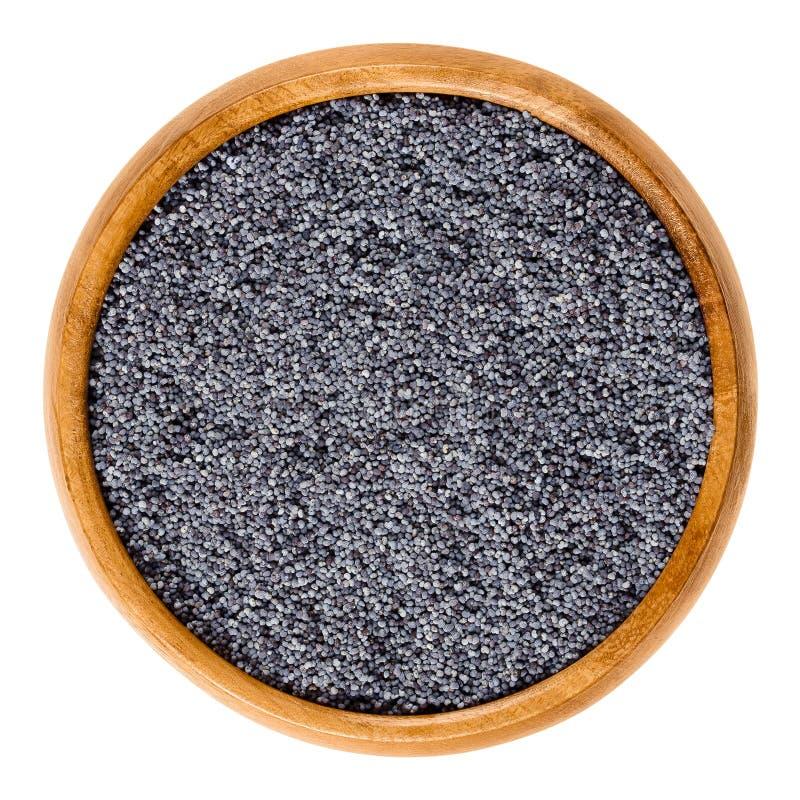 在木碗的蓝色罂粟种子在白色 免版税库存照片
