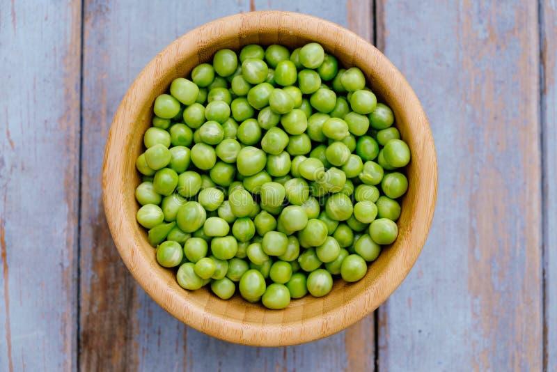 在木碗的豌豆在木背景,顶视图 免版税库存照片