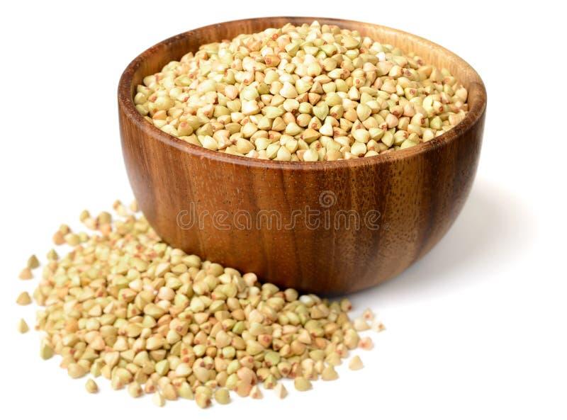 在木碗隔绝的未煮过的荞麦,在白色背景 免版税库存图片