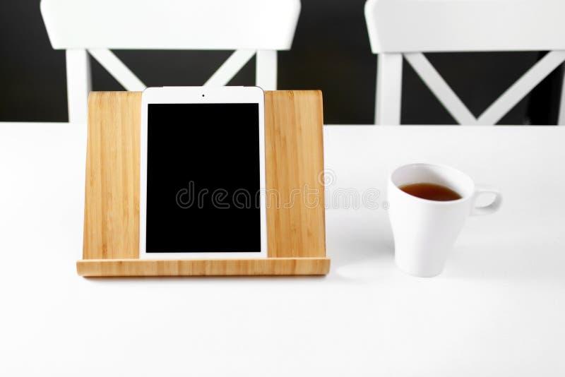 在木立场的大模型数字片剂 在一个木立场的片剂 白色杯子用茶 办公室工作场所 库存照片