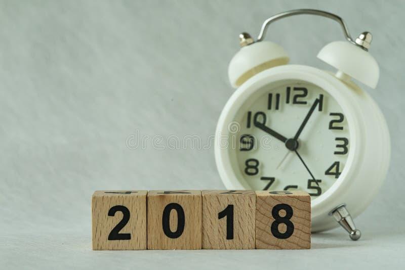 在木立方体块的选择聚焦2018年与白色闹钟 库存照片
