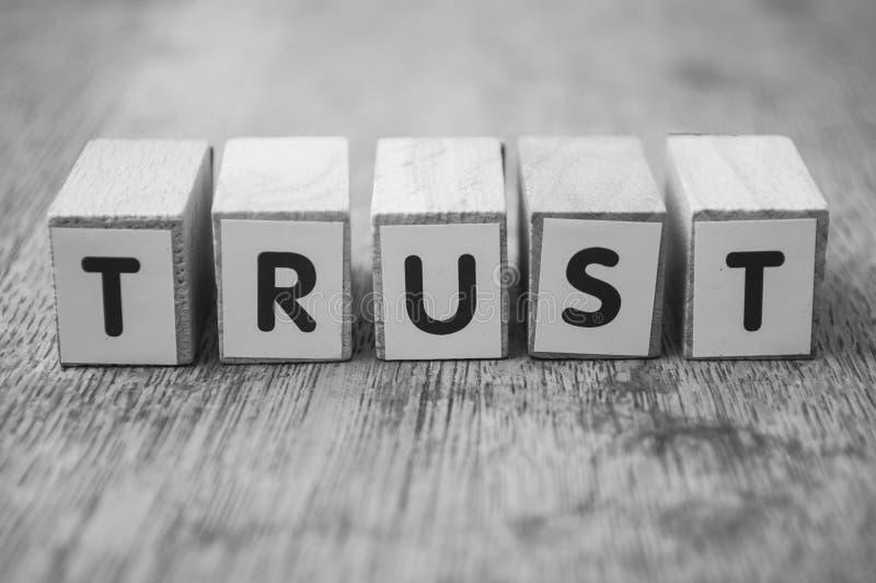 在木立方体的词在木书桌背景概念-信任 免版税库存图片